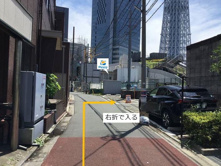 通りを右折し駐車場敷地内に入ります。前面道路は一方通行の為、左折入庫の経路はありません。