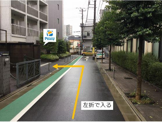 通りを左折し駐車場敷地内に入ります。前面道路は一方通行のため、右折入庫の経路はありません。前面道路は平日の7:30~9:00まで車両通行禁止ですので、ご利用時はご注意下さい。