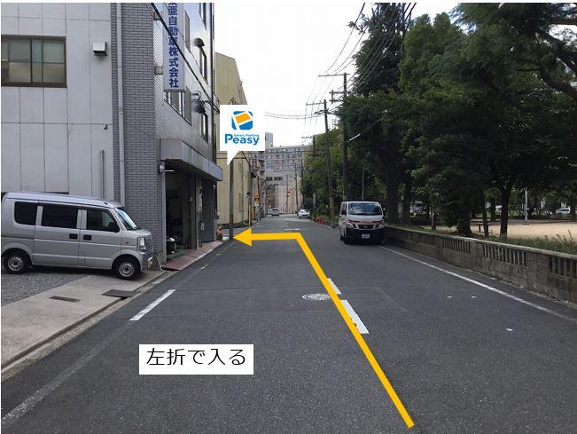 前面道路を左折して駐車場敷地内に入ります。
