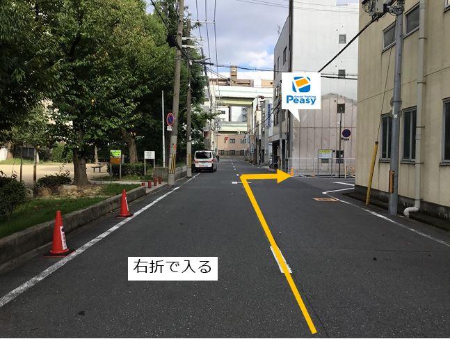 前面道路を右折して駐車場敷地内に入ります。
