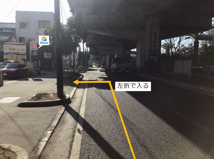通りを左折し駐車場敷地内に入ります。前面道路に中央分離帯がございます。